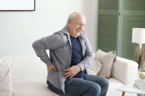 A man holding his lower back due to chronic pain.